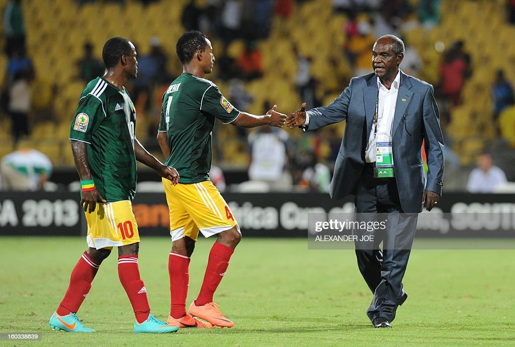 Ethiopia head coach Sewnet Bishaw (R) congratulates defender Abebaw Butako (C) and defender Berhanu Bogale on January 29, 2013 during a 2013 African Cup of Nations Group C football match against Nigeria at the Royal Bafokeng stadium in Rustenburg.