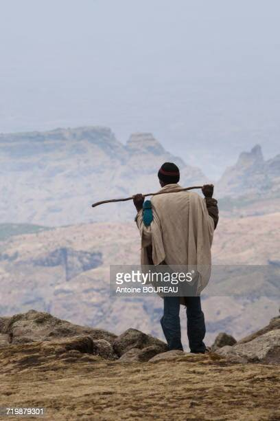 Ethiopia, Man seen from behind holding a stick on his shoulders looking at the Simien mountains