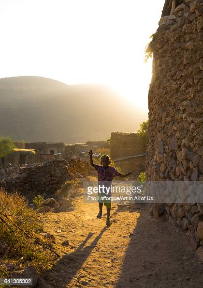 Ethiopian boy running in the streets of a traditional Argoba stone houses village near harar on January 12 2017 in Koremi Ethiopia