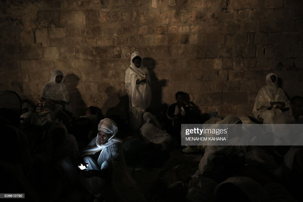 Ethiopian Christian pilgrims attend an Ethiopian Orthodox ceremony of the 'Holy Fire' at the Dir Al-Sultan Church held on the roof of the Holy Sepulcher in Jerusalem's Old City on April 30, 2016. Christian believers mark the Holy Week of Easter in celebration of the crucifixion and resurrection of Jesus Christ. / AFP / MENAHEM