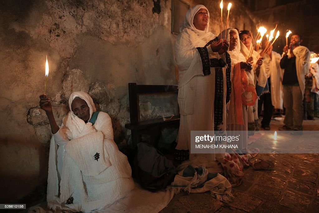 Ethiopian Christian pilgrims hold candles during an Ethiopian Orthodox ceremony of the 'Holy Fire' at the Dir Al-Sultan Church held on the roof of the Holy Sepulcher in Jerusalem's Old City on April 30, 2016. Christian believers mark the Holy Week of Easter in celebration of the crucifixion and resurrection of Jesus Christ. / AFP / MENAHEM