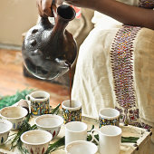 Pouring fresh coffee from a Buna Pot for the Ethiopian coffee ceremony.