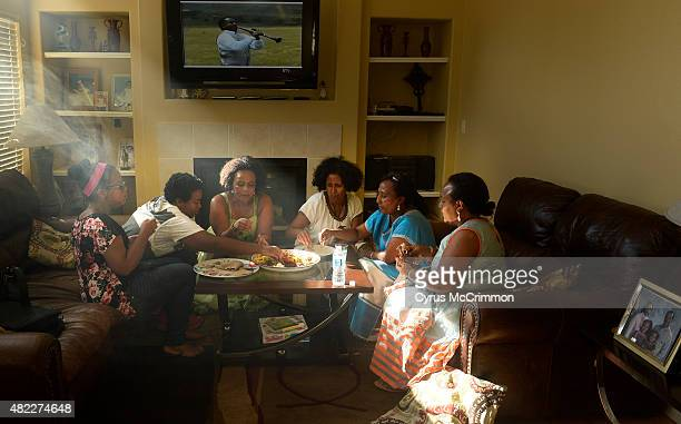 Ethiopian families gather around the coffee table in the living room at a home in Aurora for a meal on Tuesday July 28 2015 They will be...