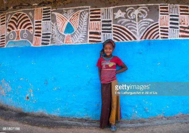 Ethiopian girl standing in front of her traditional painted house Kembata Alaba Kuito Ethiopia on March 9 2016 in Alaba Kuito Ethiopia