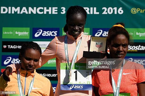 Ethiopian Gulume Chala Kenyan Visiline Jepkesho and Ethiopian Dinknesh Tefera pose on the podium of the 40th Paris Marathon on April 3 2016 in Paris...