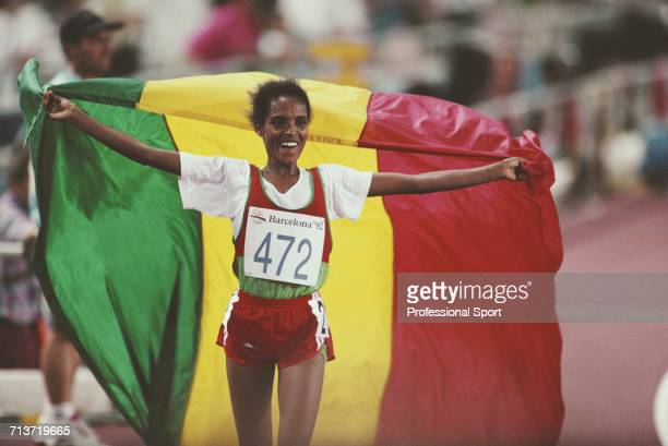 Ethiopian long distance runner Derartu Tulu celebrates with the national flag of Ethiopia after crossing the finish line in first place to win the...