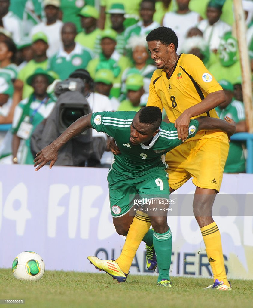 Ethiopian midfielder Mekersa Asrat (R) vies for the ball with Nigerian attacker Emmanuel Emenike during the FIFA World Cup qualifier in Calabar on November 16, 2013. Nigeria defeated Ethiopia 2-0 and qualified for the FIFA 2014 World Cup in Brazil. AFP PHOTO/PIUS UTOMI EKPEI