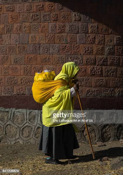 Ethiopian monk woman walking with a heavy bag on her back on January 18 2017 in Lalibela Ethiopia