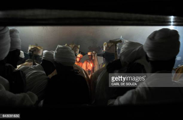 Ethiopian Orthodox Christian priests hold candles on January 21 2012 during mass in an frankincensefilled tent during the annual festival of Timkat...
