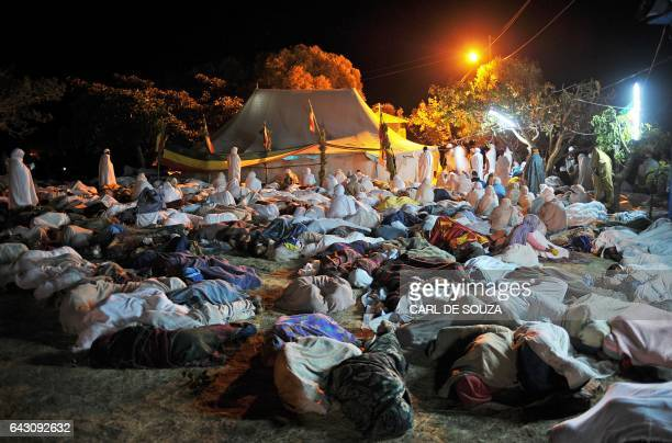 Ethiopian Orthodox Christian sleep and pray outside a tent containing a tabot from the church of SaintMichael on January 21 2012 during the annual...