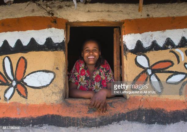 Ethiopian woman standing in the window of her traditional painted house Kembata Alaba Kuito Ethiopia on March 11 2016 in Alaba Kuito Ethiopia