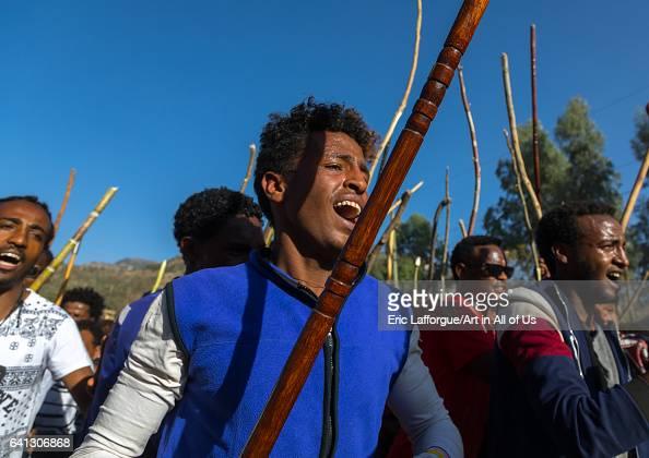 Ethiopian young men dancing and singing in the street with sticks during Timkat epiphany festival on January 18 2017 in Lalibela Ethiopia