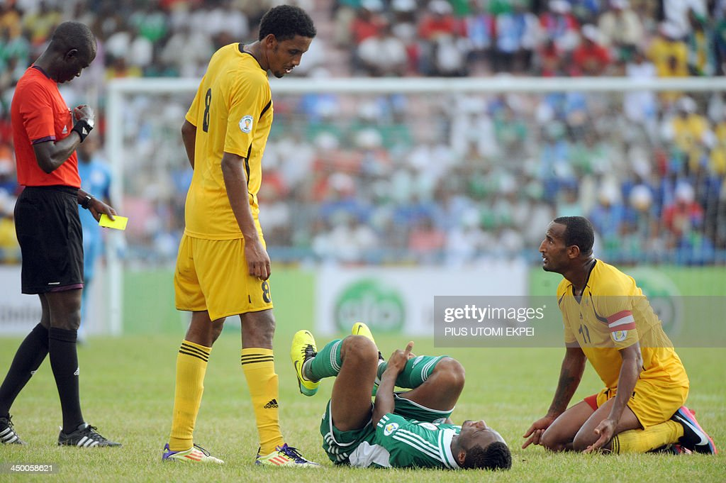 Ethiopia's Girma Adane (R) kneels on the ground as Gambian referee Bakary Gassama (L) prepares a yellow card for a foul on Nigerian midfielder Mikel Obi (2nd R) during the FIFA World Cup qualifier in Calabar on November 16, 2013. Nigeria defeated Ethiopia 2-0 and qualified for the FIFA 2014 World Cup in Brazil.