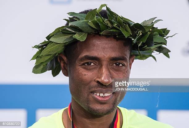 Ethiopia's Kenenisa Bekele poses with his laurels on the podium after winning the 43rd Berlin Marathon in Berlin on September 25 2016 / AFP / John...
