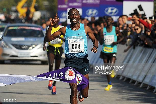 Ethiopia's Tadese Tola Woldegeberel crosses the finish line to win the men's portion of the Beijing Marathon in the Chinese capital on October 20...
