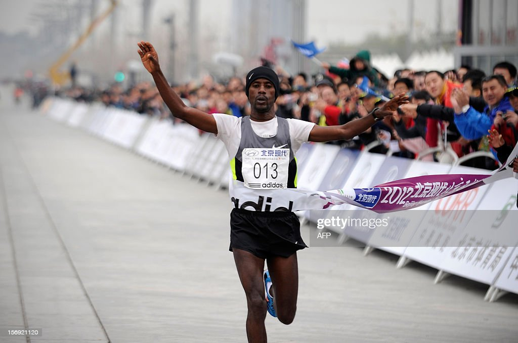 Ethiopia's Tariku Jufar Robi crosses the finish line to win the men's portion of the Beijing Marathon in the Chinese capital on November 25, 2012. A total of 30,000 runners took part in the race. AFP PHOTO / WANG ZHAO