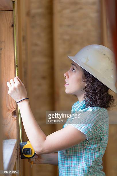 Ethnic adult female measuring a window frame