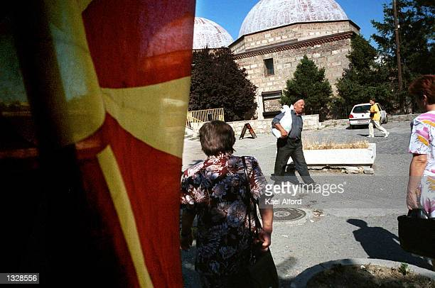 Ethnic Albanian and Slavic Macedonians pass between a Macedonian flag and an Ottoman era building at the foot of a bridge betweenAlbanian and...