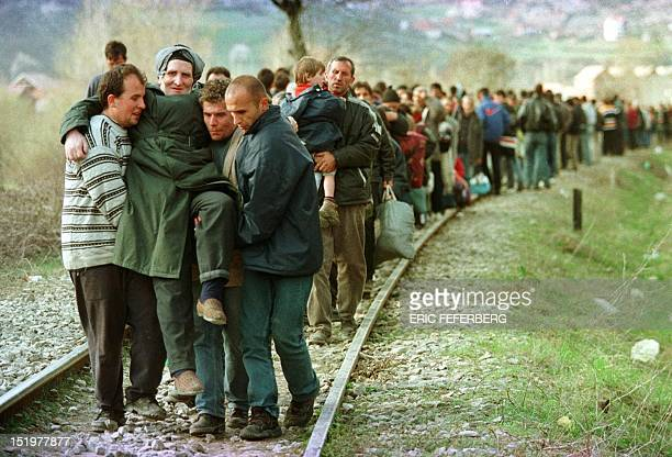 Ethnic Albanian refugees arrive by foot in Macedonia 01 April 1999 after being forced at the Kosovar village of Djeneral Jankovic to leave a train...