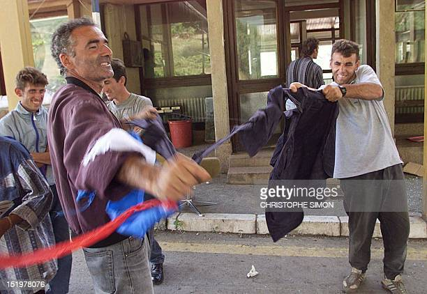 Ethnic Albanian refugees from Kosovo tear up a Serb uniform and flag 13 June 1999 after crossing into Serbia at the Morina border point after German...