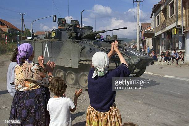 Ethnic Albanians from Kosovo applaud as a British tank passes in a street of Pristina 13 June 1994 Some 16000 British troops moved into Kosovo...