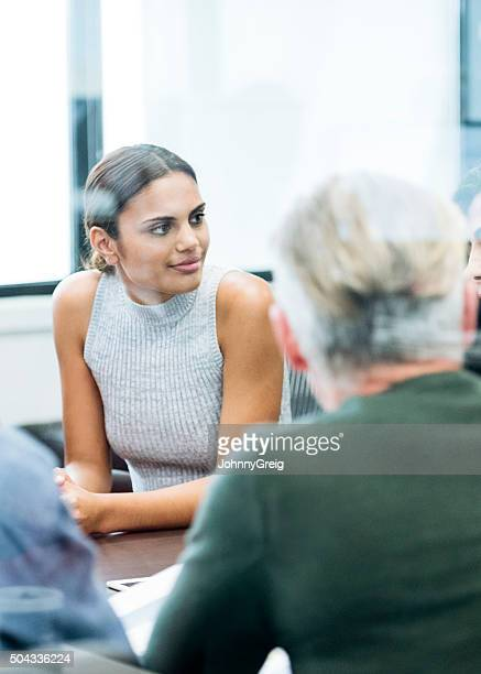 Ethnic businesswoman in business meeting looking away
