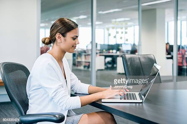 Ethnic businesswoman using laptop at desk in modern office