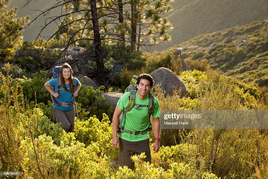 Ethnic couple on a backpacking trip hiking in the mountains through chaparral and pine trees.