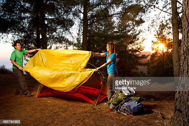 Ethnic couple putting a rainfly on a tent while backpacking in the mountains.