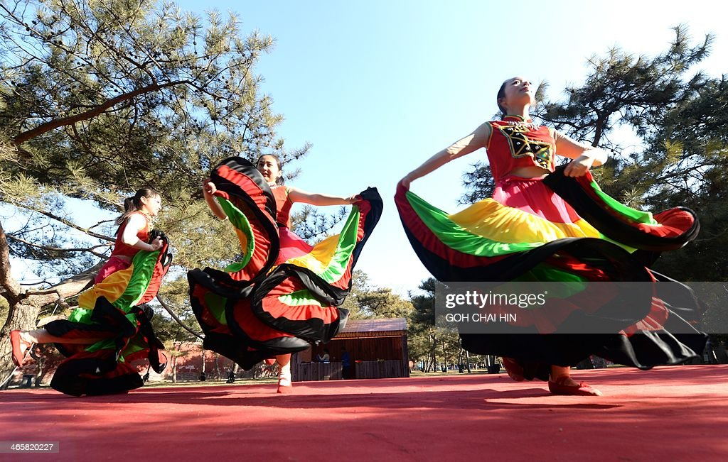 Ethnic dancers from southwest China's Yunnan province perform at the Ditan park temple fair in Beijing on January 30, 2014, on the eve of the Lunar New Year. Over a billion Chinese in China and millions more all over the world will be celebrating the Lunar New Year, known as the Spring Festival in China. AFP PHOTO/GOH CHAI HIN