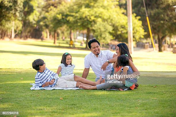 Ethnic family sitting on a blanket at the park