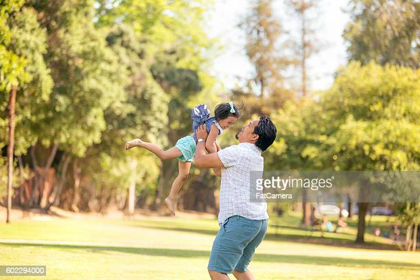 Ethnic father tossing his daughter in the air