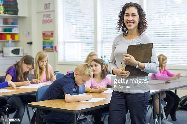 Ethnic female elementary teacher posing in front of classroom