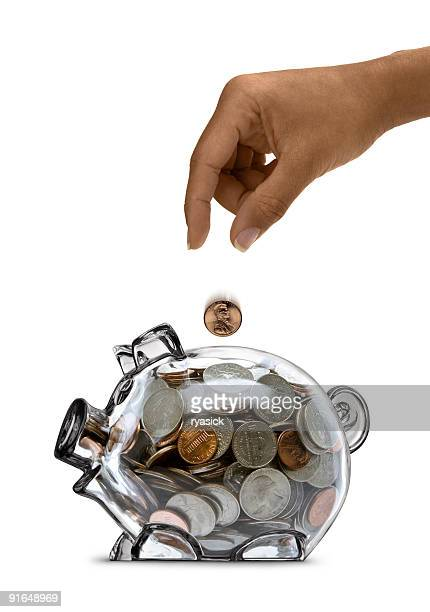 Ethnic Female Hand Dropping Coin into Full Clear Piggy Bank
