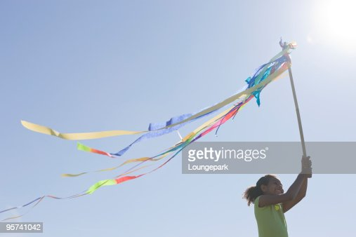 Ethnic girl holding up pole of blowing streamers : Stock Photo