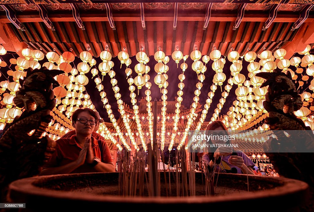 Ethnic Malaysian-Chinese devotees offer prayers and burn joss sticks at the Thean Hou temple decorated with red lanterns in Kuala Lumpur on February 7, 2016, on the eve of the Lunar New Year. The Lunar New Year will mark the start of the Year of the Monkey on February 8. AFP PHOTO / MANAN VATSYAYANA / AFP / MANAN VATSYAYANA