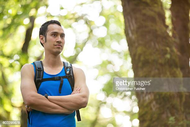 Ethnic male wearing a hydration pack in the woods