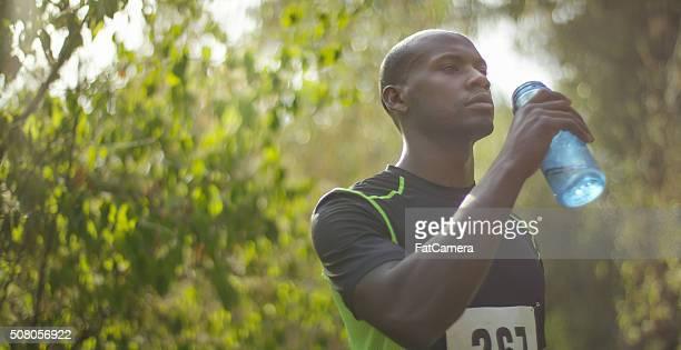 Ethnischen Mann Trinkwasser nach dem Rennen