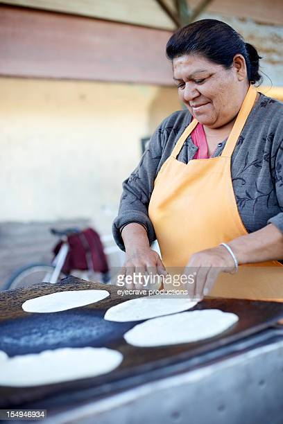 メキシコの女性民族の小麦粉トルティーヤ焼く