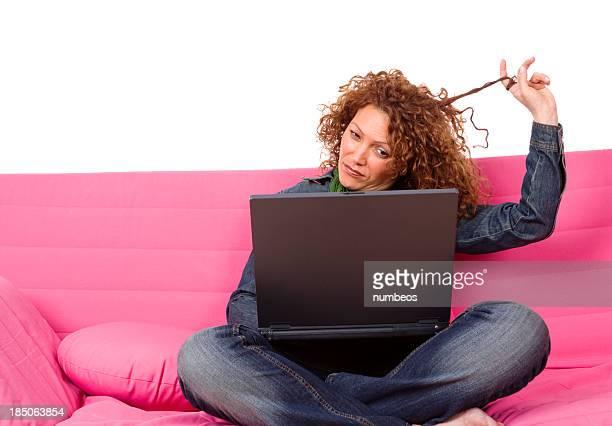 Ethnique milieu adulte femme à l'aide d'un ordinateur portable sur un canapé