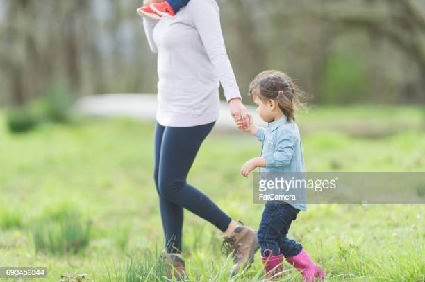 Ethnic mom outside on farm with her daughter and flock of chickens
