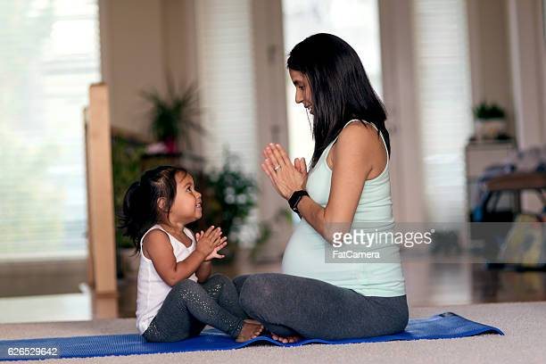 Ethnic mother and daughter meditating together on yoga mat
