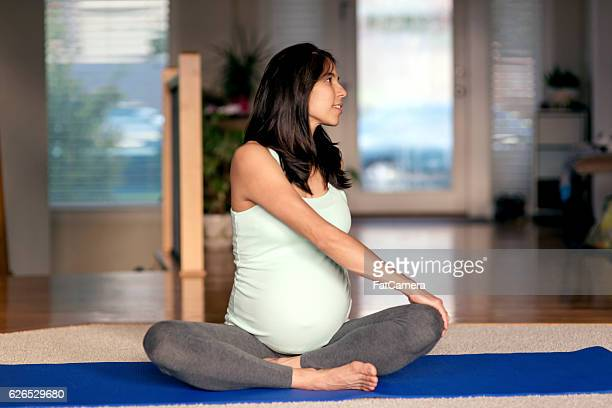 Ethnic mother stretching while sitting on yoga mat at home