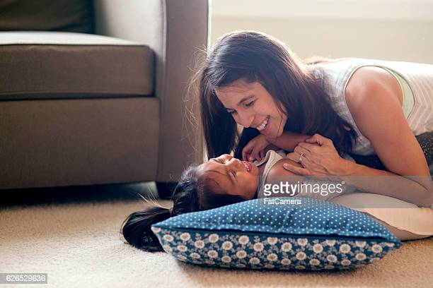 Ethnic mother tickling her cute daughter on the carpeted floor