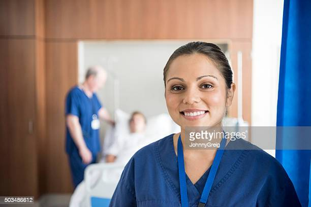 Ethnic nurse on hospital ward smiling to camera, portrait