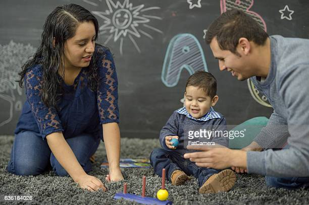 Ethnic parents reading with their toddler in a home playroom