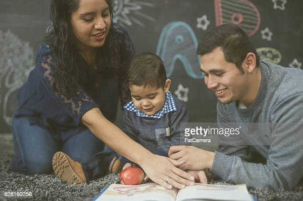 Ethnic parents reading with their toddler in a playroom