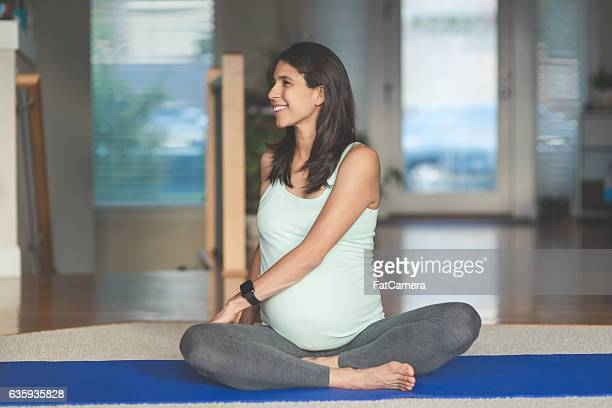 Ethnic pregnant mother doing yoga in the home