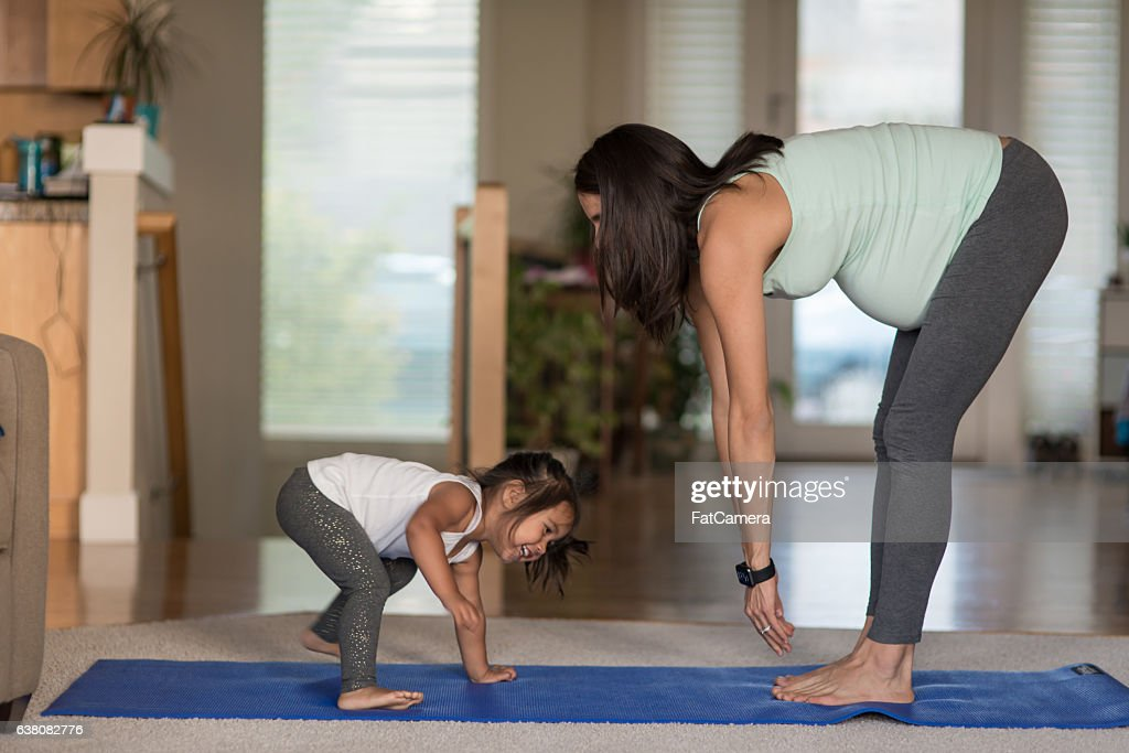 Ethnic pregnant mother doing yoga with her young toddler : Stock Photo