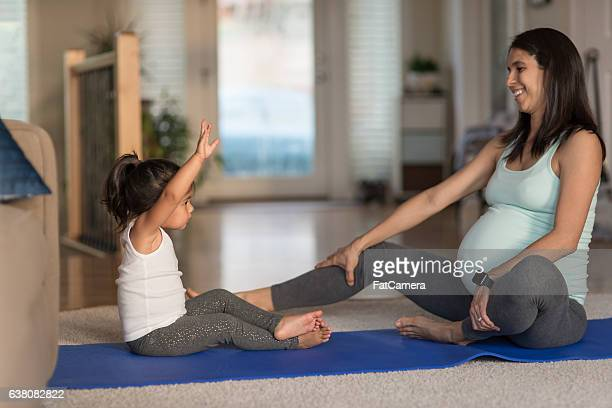 Ethnic pregnant mother doing yoga with her young toddler